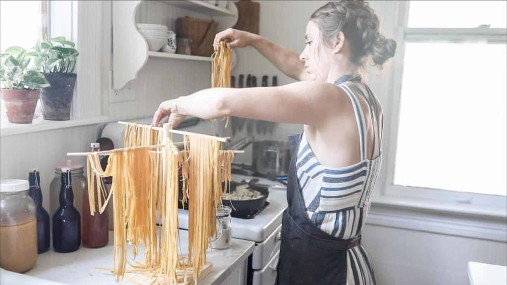 women placing homemade pasta from the pasta drying rack to a pot of boiling water
