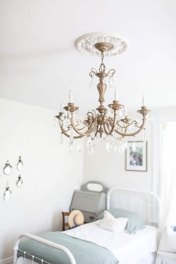 gold victorian chandelier with crystals hands in a girls room