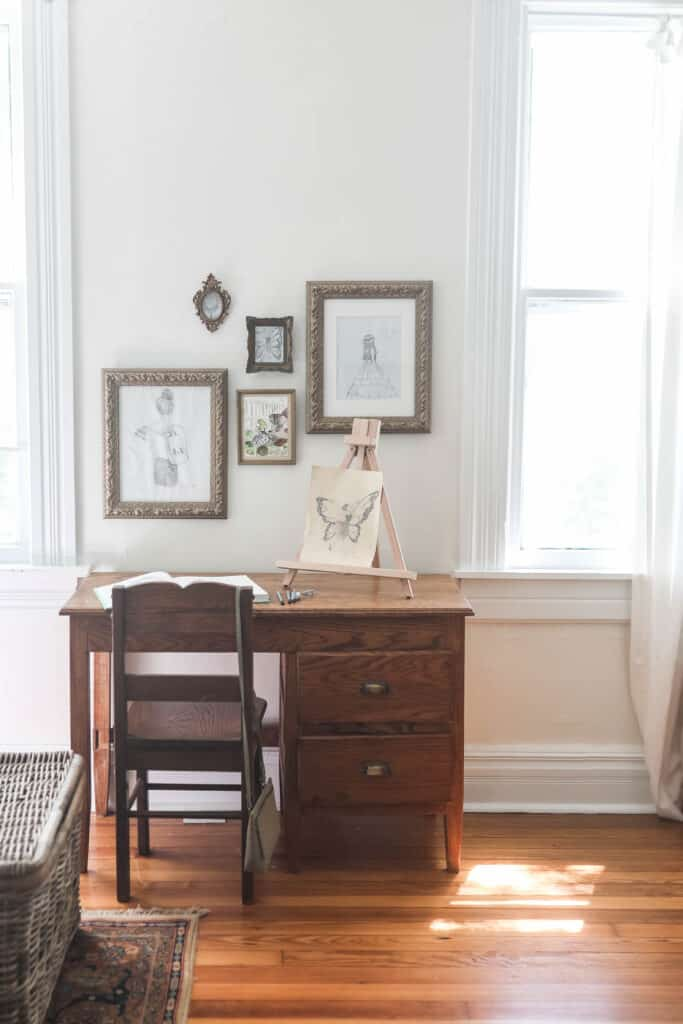 handmade wooden desk with brass handles. Gallery wall of drawings in gold frames are above the desk