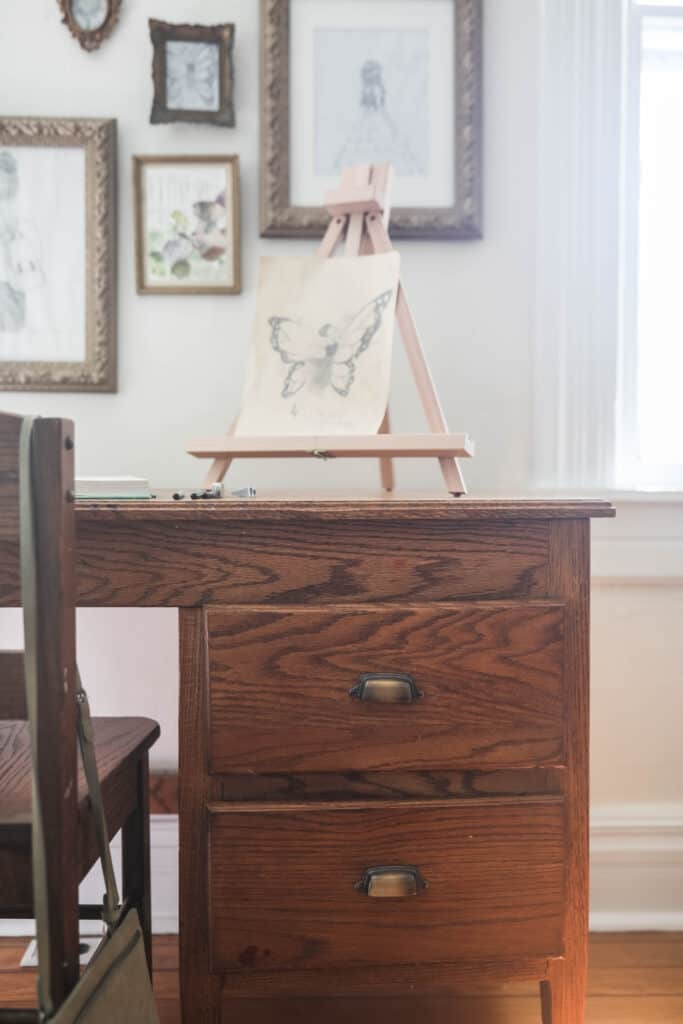 wooden desk with an easel with a drawing on it