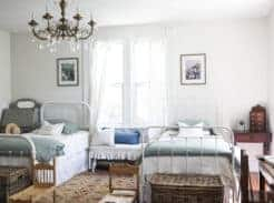 victorian farmhouse girls room with two twin beds and a gold chandelier