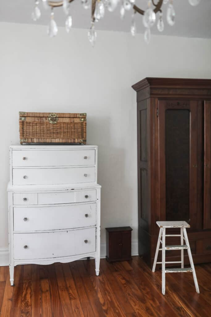 white antique dresser with a wicker chest on top. To the right in a wood armoire