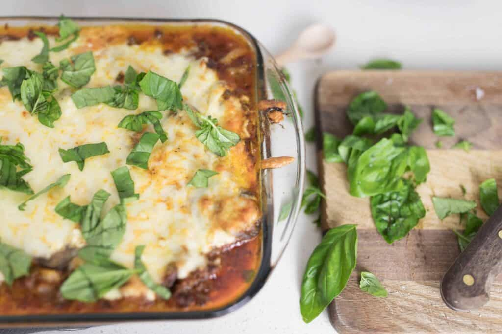 zucchini lasagna in a baking dish covered with fresh basil. A cutting board to the right with basil