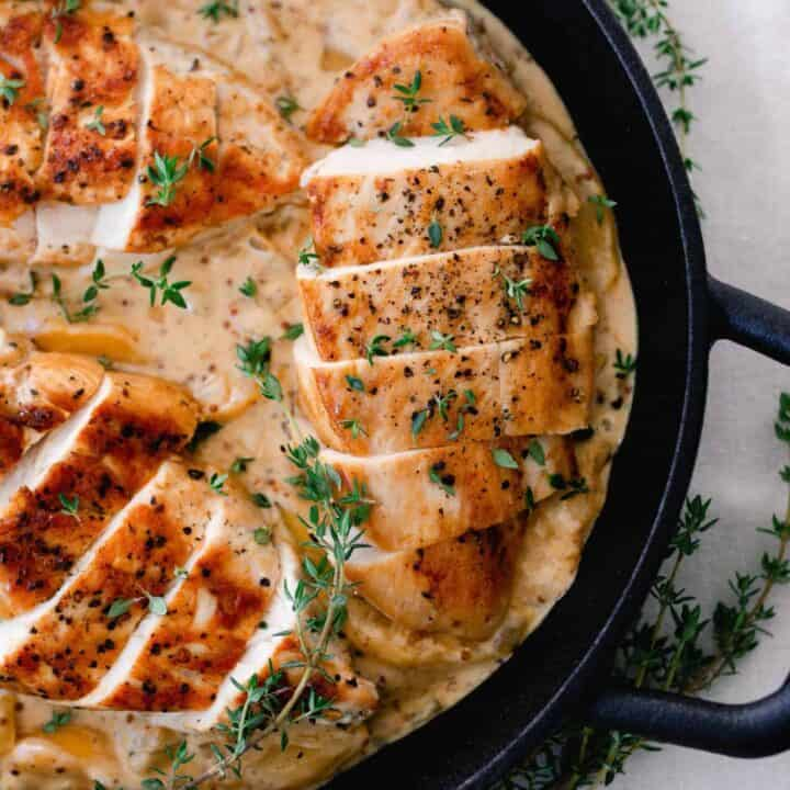 seared chicken breasts in a creamy peach sauce topped with herbs in a cast iron skillet