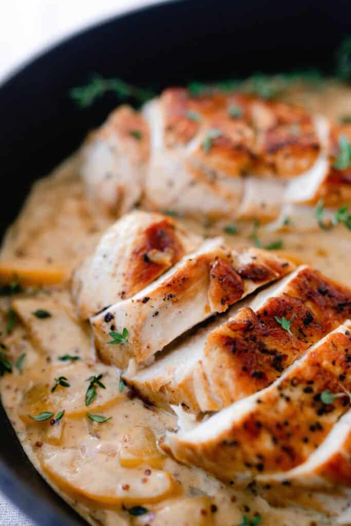 sliced chicken breasts on top of a creamy peach sauce
