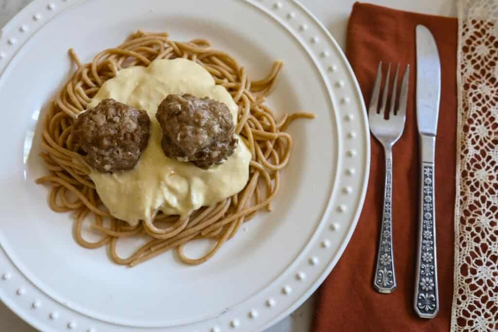 einkorn spaghetti topped with creamy pumpkin sauce and two sausage meatballs on a white plate. A red napkin with a knife and a fork are to the right of the plate