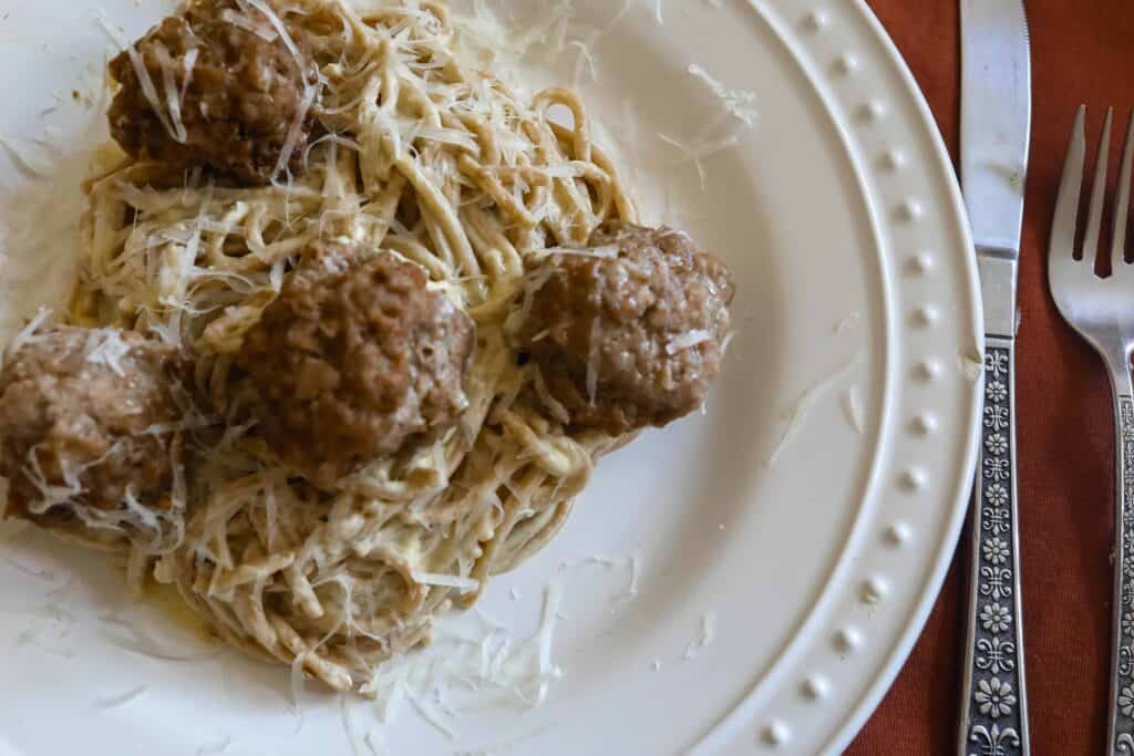 overhead photo of creamy pumpkin pasta sauce with spaghetti noodles and sausage meatballs on a white plate