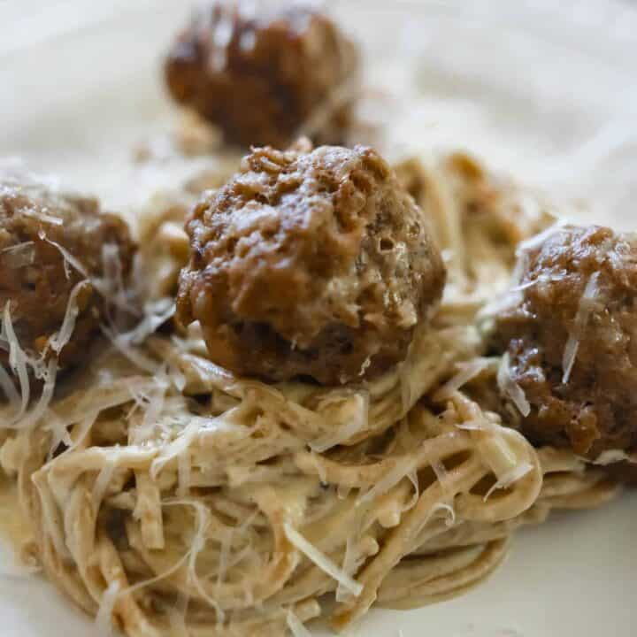 creamy pumpkin sauce tossed with einkorn spaghetti and topped with sausage meatballs on a white place