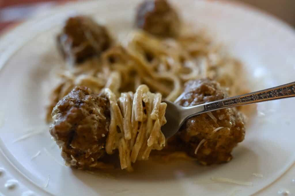 fork with spaghetti twirled around it and a meatball at the end on a plate with more pasta