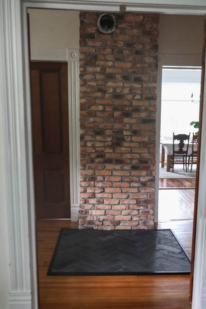 front view of a brick chimney with a DIY hearth pad made from slate in a herribone pattern