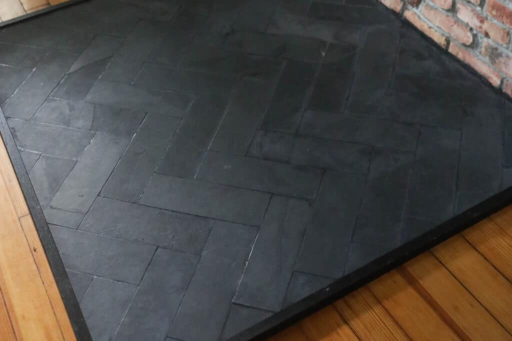 close up picture of a DIY hearth pad with slate tile in a herringbone pattern