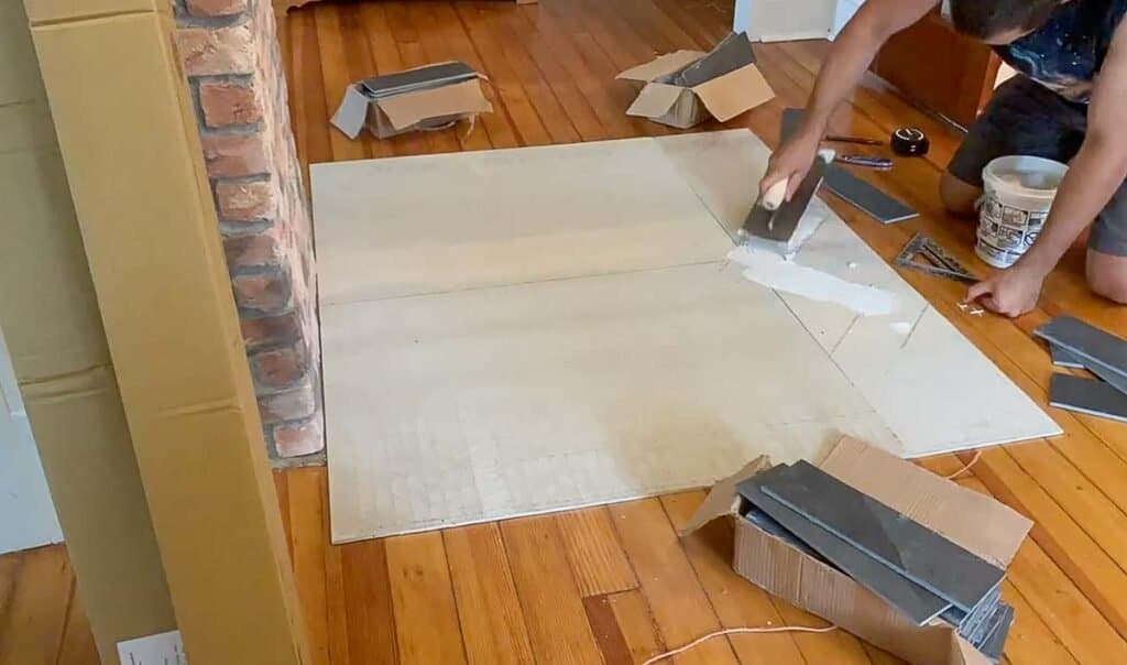 adding thinset tile adhesive to backer board to lay tile