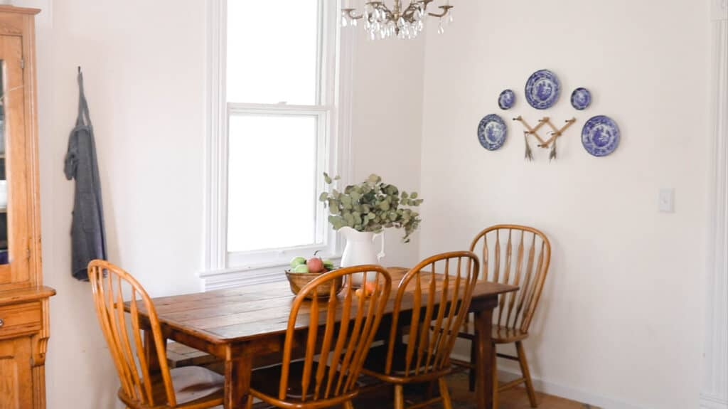 farmhouse table with 4 wooden chairs with a pitcher of eucalyptus and a basket full of hand picked apples