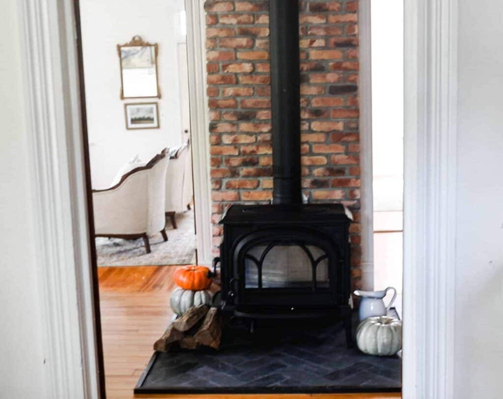 wood stove with a brick chimney and diy hearth pad with black slate
