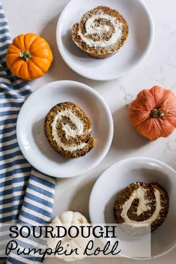 three slices our sourdough pumpkin rolls on white plates with pumpkins spread around