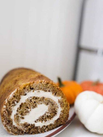 sourdough pumpkin roll with cream cheese filling on a white plate with orange and white pumpkins to the right