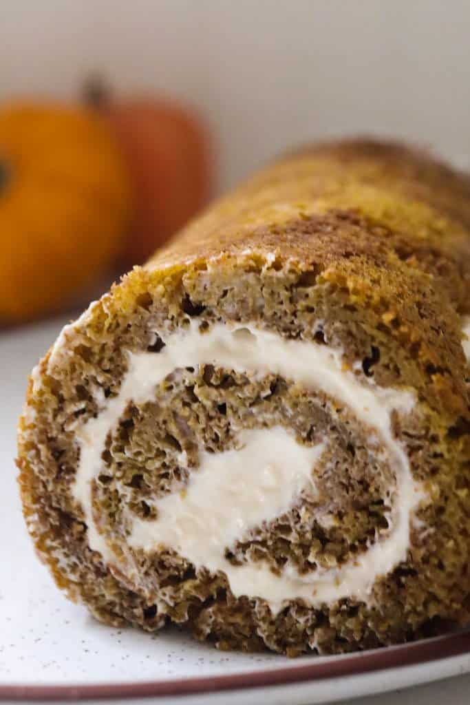 sourdough pumpkin roll with cream cheese frosting rolled into a log and placed on a white plate