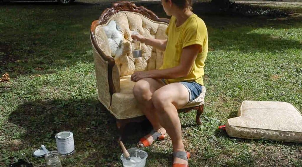women wearing yellow shirt spraying chalk painted chair with water