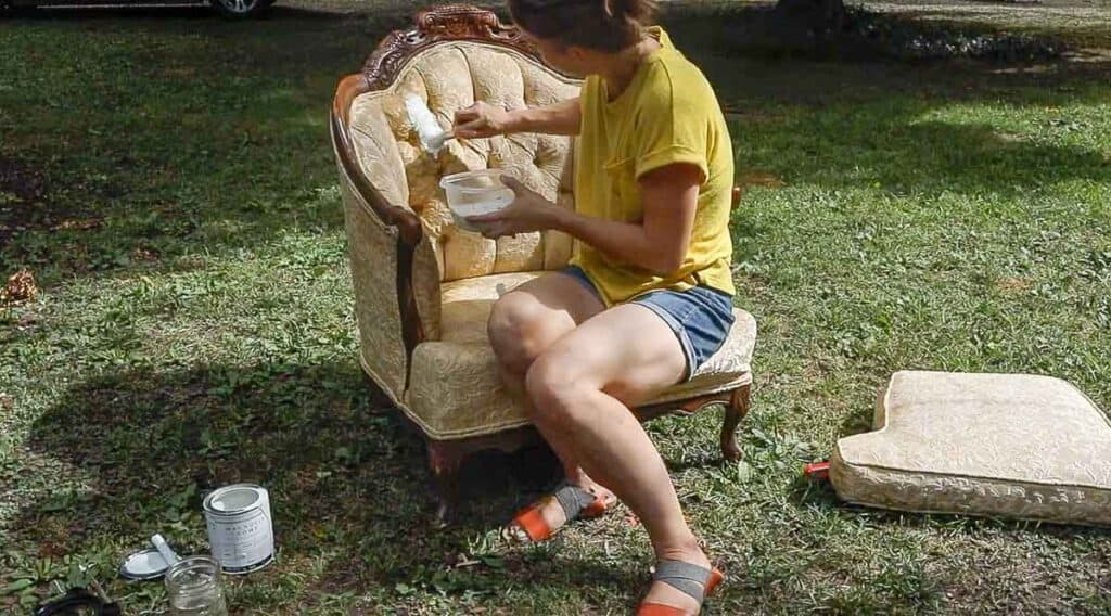 women wearing a yellow shirt chalk painting a victorian chair