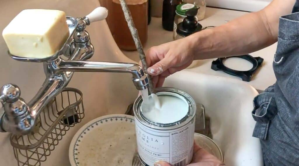 adding water to chalk paint in a farmhouse sink