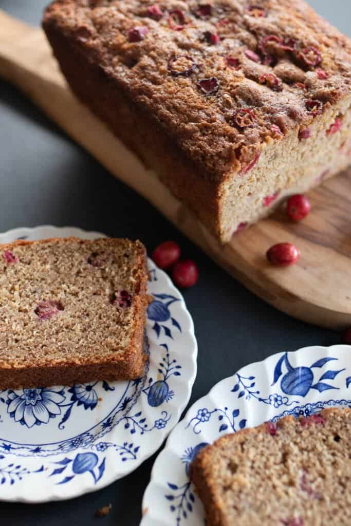 sourdough cranberry bread slices on two white and blue plates. The remaining bread is on a wood cutting board in the background