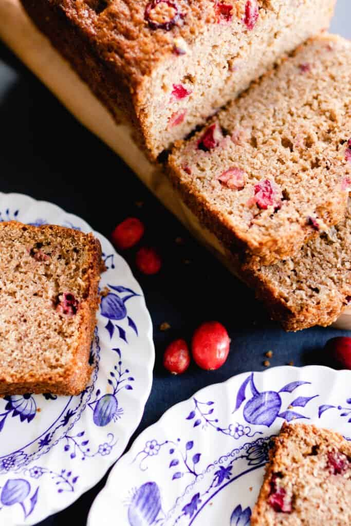 sourdough orange cranberry bread sliced on a wood cutting board with two white and blue plates with slices of bread.