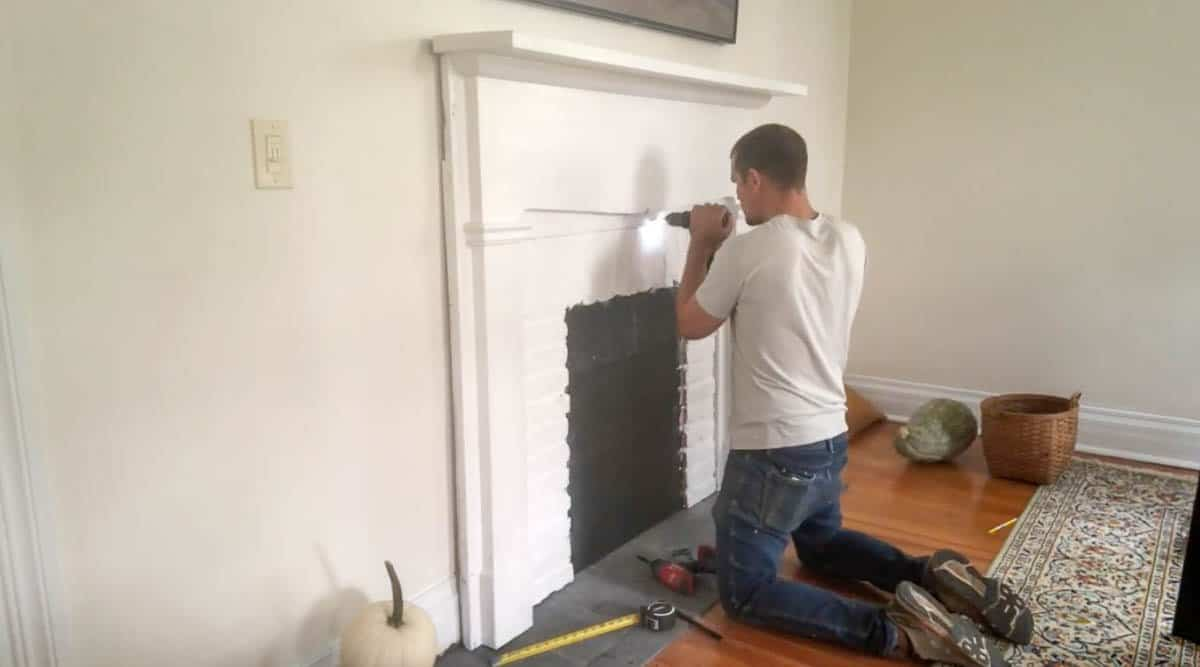man securing faux fireplace to the wall with screws