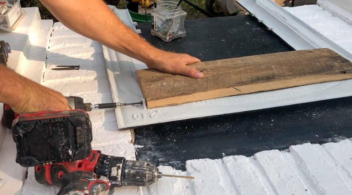 man drilling 1x6 to the back of a fireplace insert