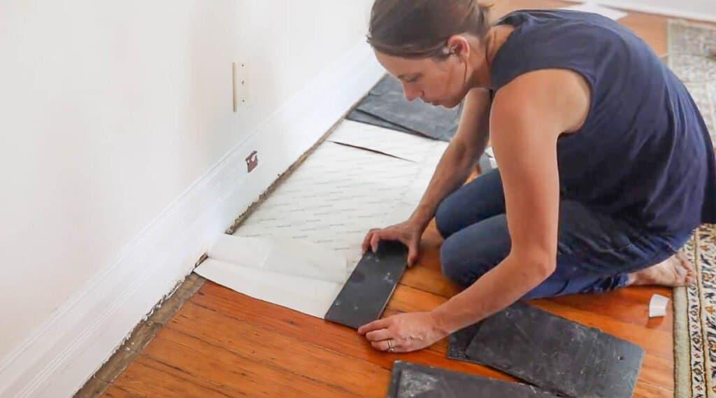women laying slate tile on tile adhesive pad to make a hearth