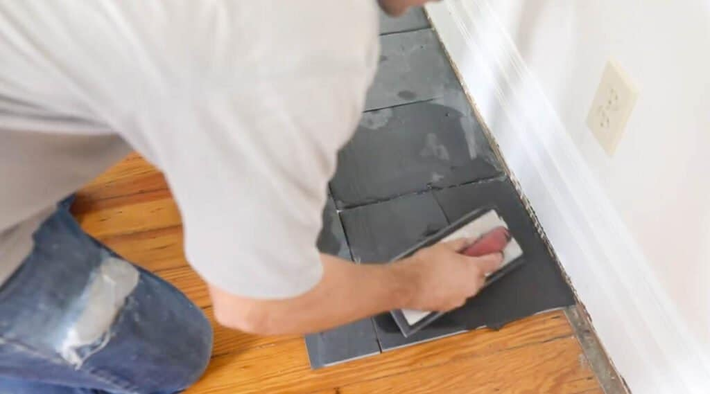 man grouting slate tile to make a fireplace hearth