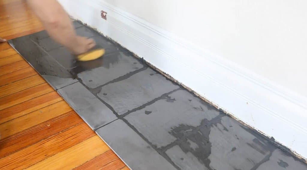 man wiping excess grout off with a wet sponge