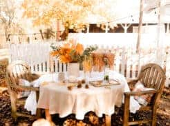 wooden table with tan linen table cloth with a crock of dried leaves and eucalyptus with a picnic basket with a barn with a picket fence in the background