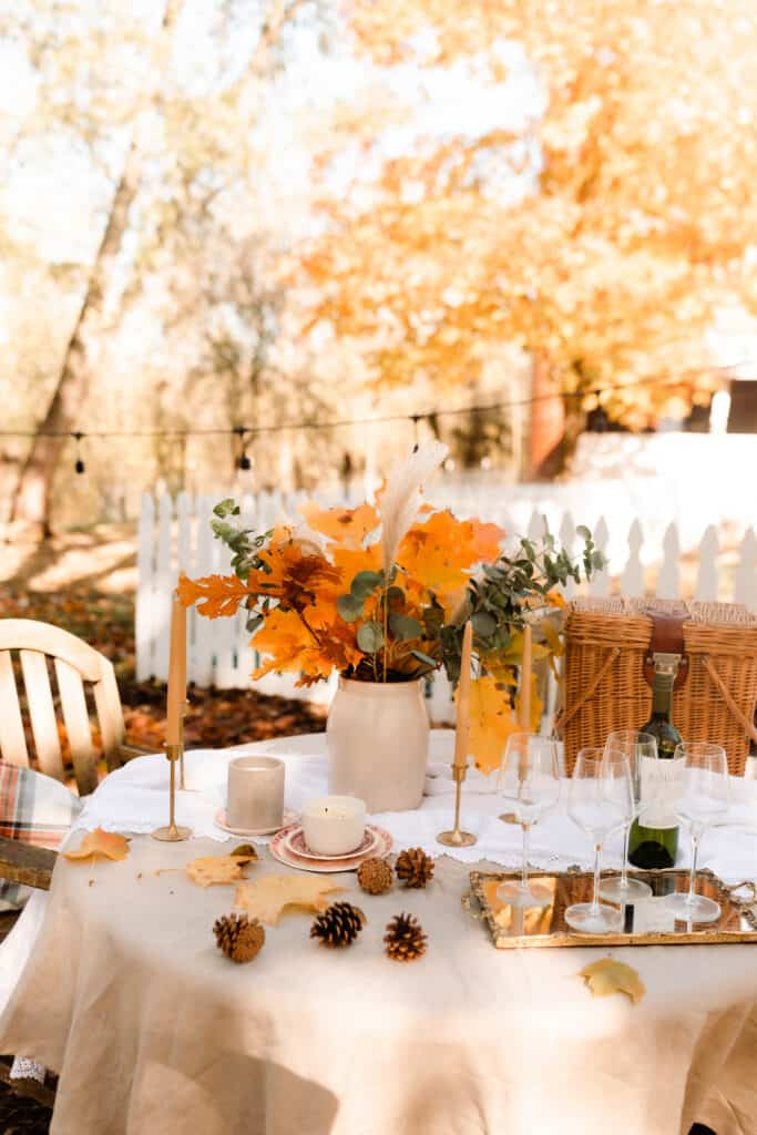 fall table setting outside on a farm. Table is covered with a tan linen table cloth, wine glasses on an antique mirrored tray, crock of dried leaves and eucalyptus and beeswax pillar candles in gold candlesticks