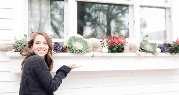 women standing next to a fall window box full of beautiful fall foliage