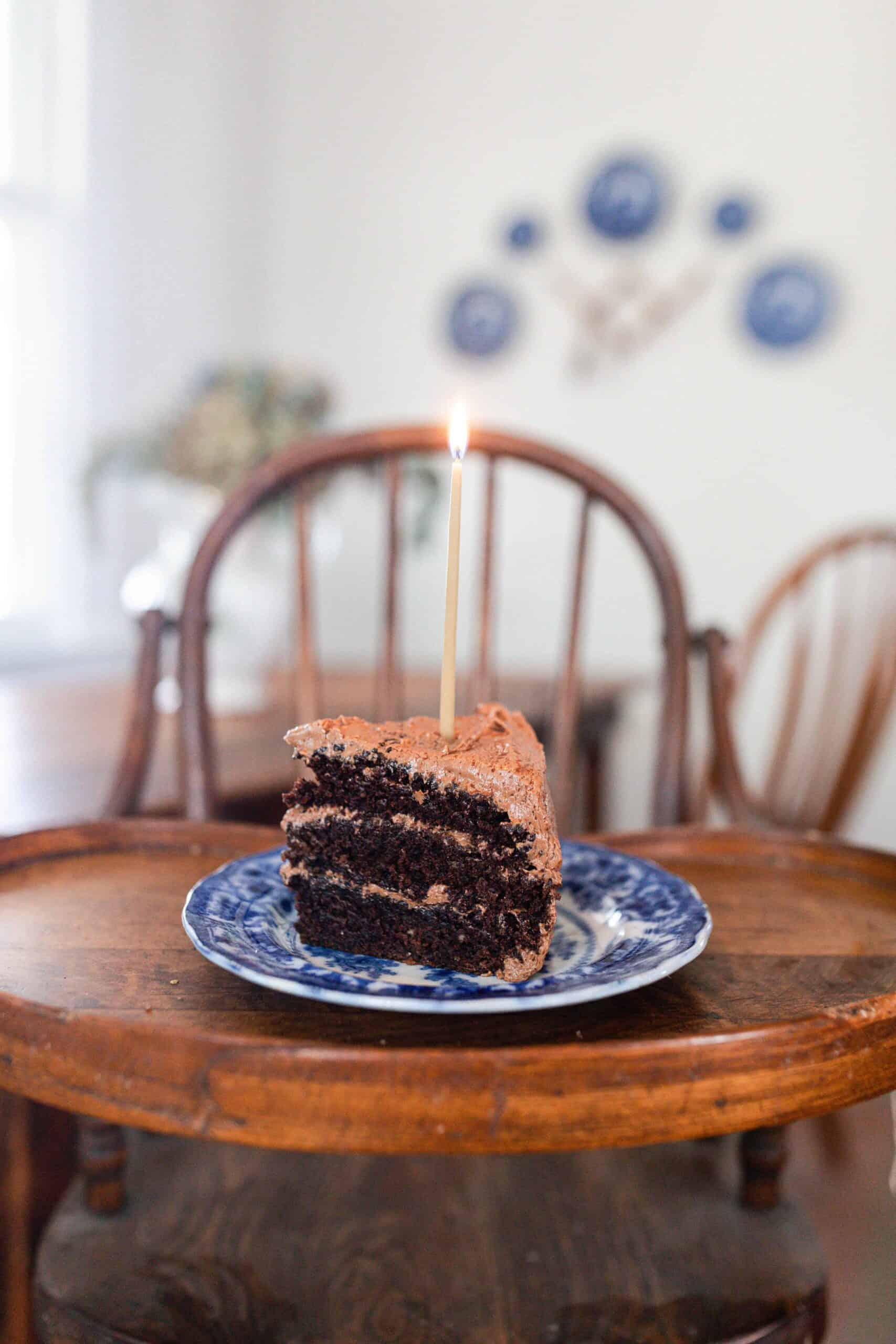 slice of three layer sourdough chocolate cake with chocolate frosting on a blue and white antique plate with a candle on a antique wooden high chair