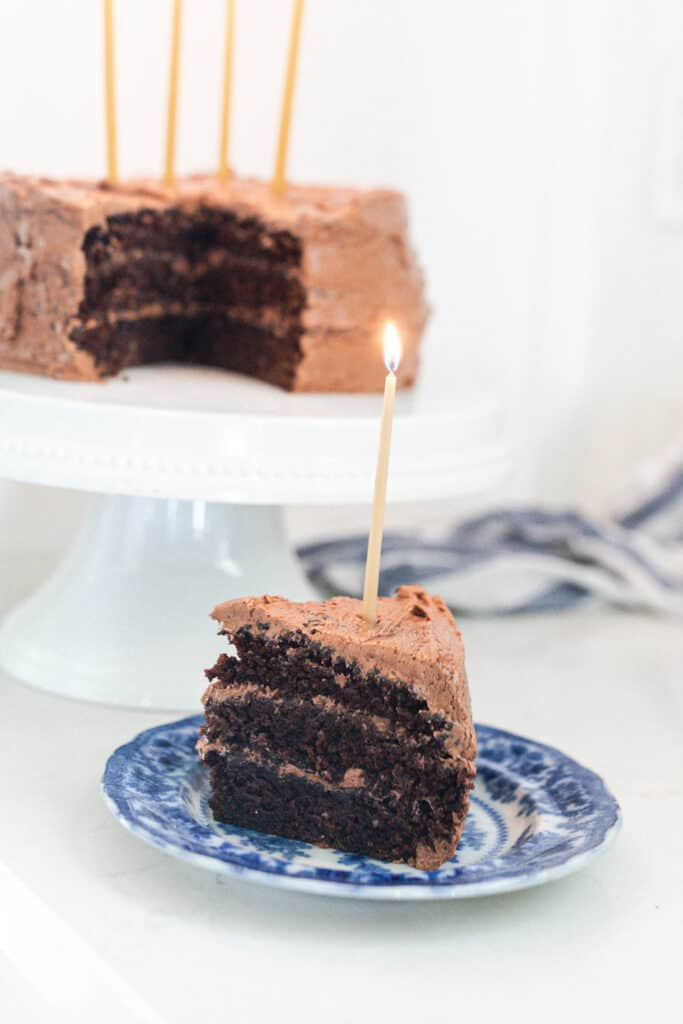 slice of three layer sourdough cake with chocolate frosting on a blue and white antique plate with the remaining cake on a white cake stand in the background