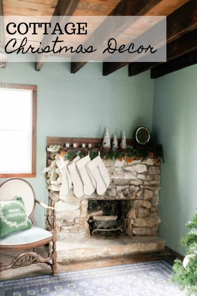 stone fireplace mantle hung with garland and stockings with a vintage chair with a Christmas pillow to the left