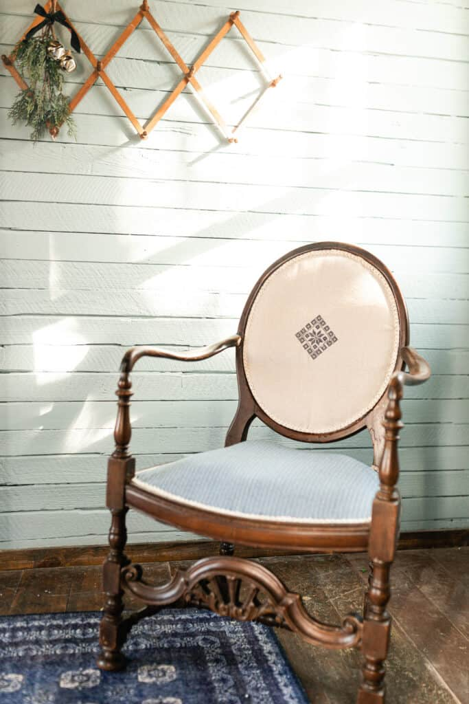 redone antique chair on a blue Turkish inspired rug with an accordion coat hanger hanging on the wall
