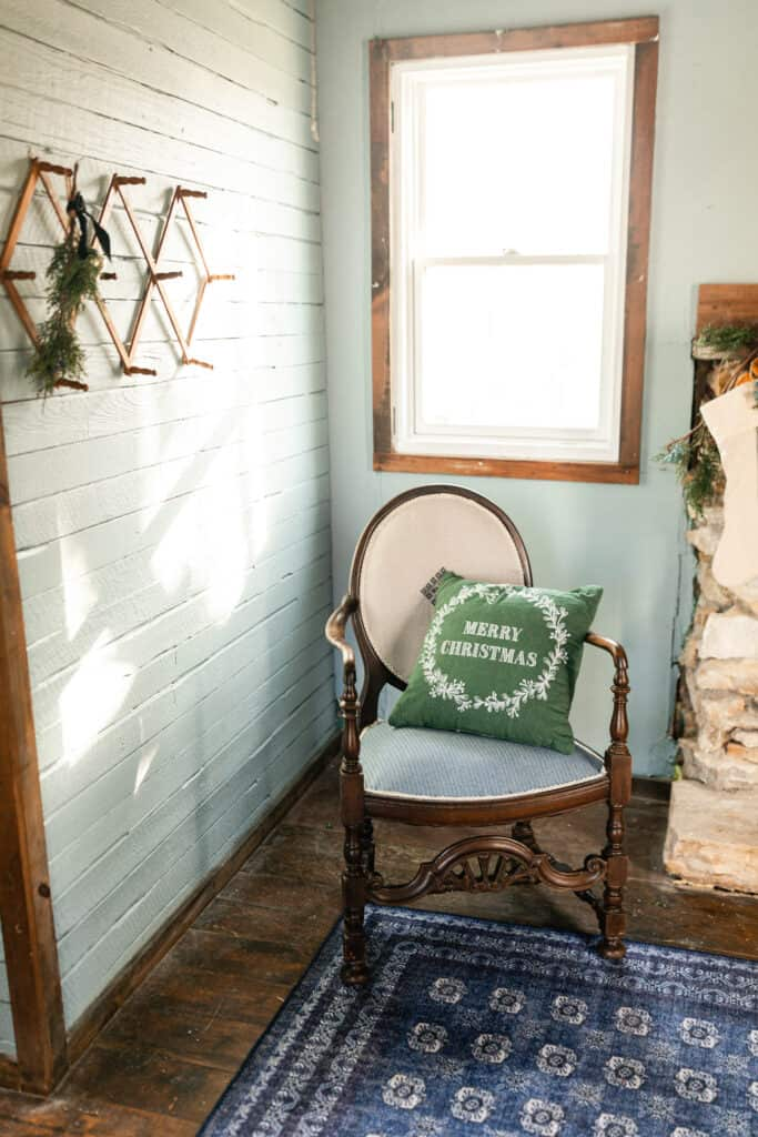antique chair with a green Christmas pillow with a accordion coat hanger to the left with some greenery and bells hanging front it