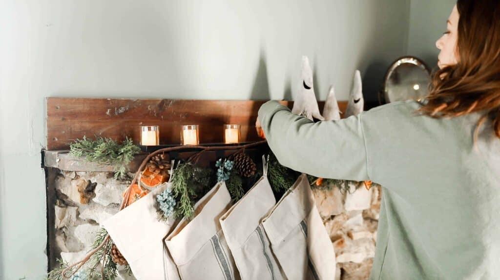 women hanging burlap stockings on a cottage stone mantle