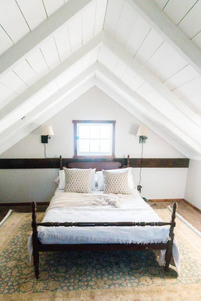 upstairs of a cottage painted white with a antique bed covered in a comfy quilt and vintage pillows