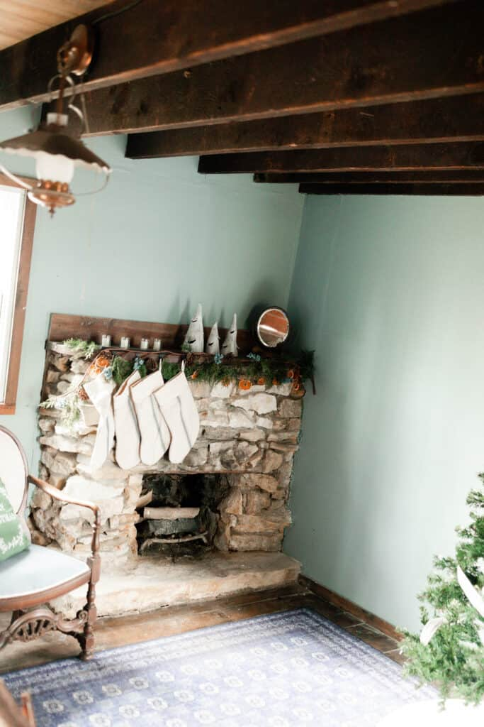 stone fireplace with a wood mantle decorated for a cottage Christmas with garland and burlap stockings