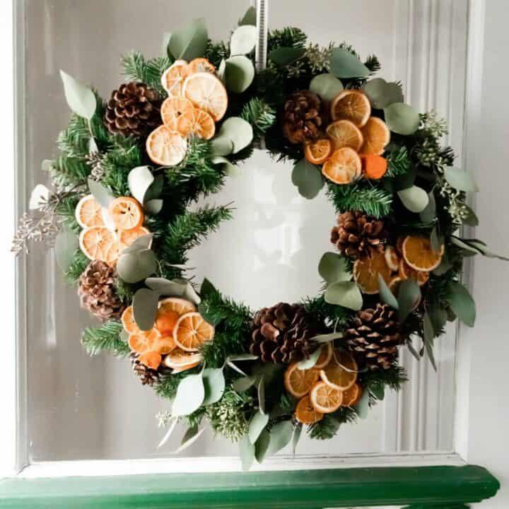 dried eucalyptus and orange wreath hanging ion a vintage door