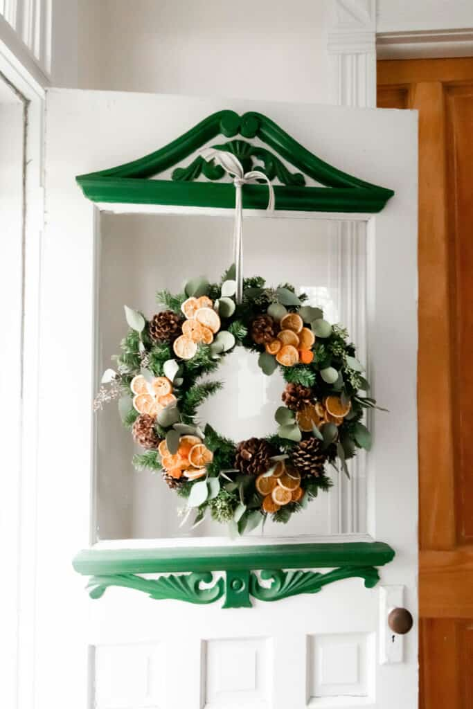 dried eucalyptus wreath with dried oranges and pinecones hanging on a vintage victorian door