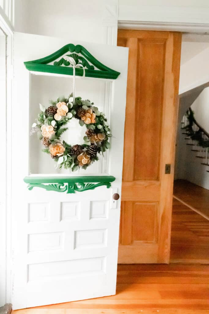 antique white and green door with a diy Christmas wreath hanging by ribbon