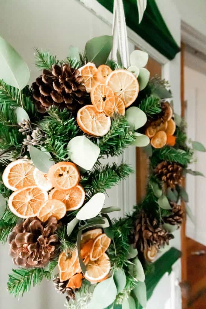 side view of a DIY Christmas wreath made with eucalyptus, dried oranges and pine cones