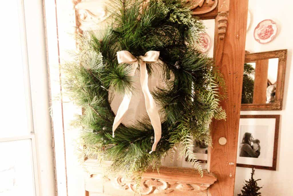 greenery wreath with a cream colored bow hung on a antique wood door