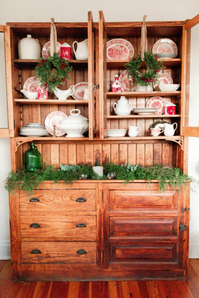 red and white plates, Christmas village houses and white vases and serving platter fill a wooden antique China cabinet. Green garland fill the cabinet countertop and wreaths hang with ribbon