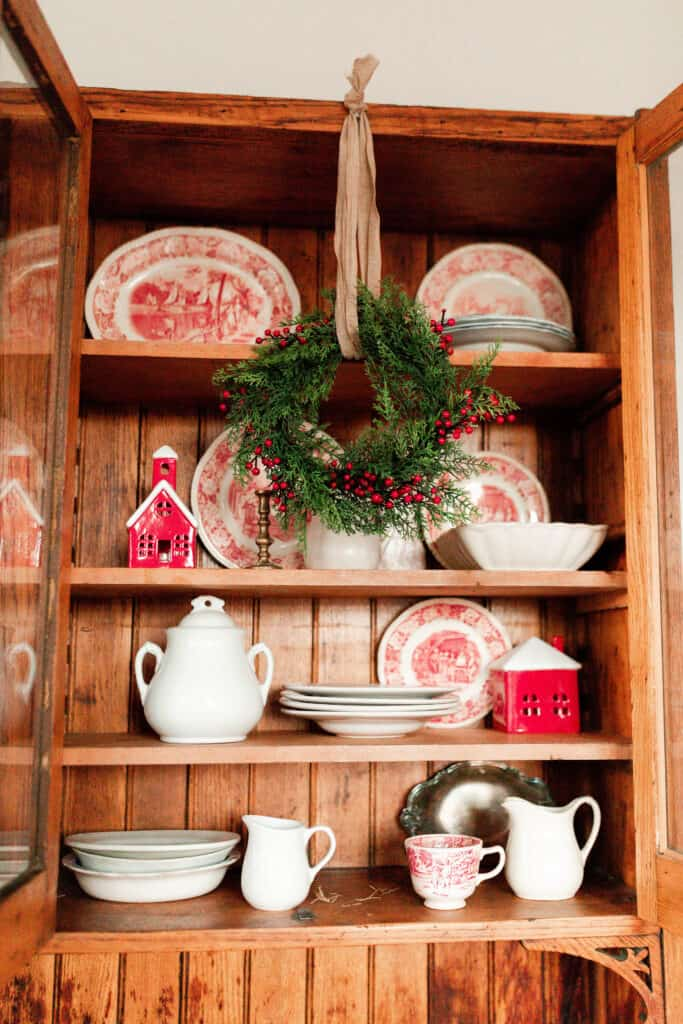 red and white vintage plates, white vases, and small red and white Christmas houses in a wood cabinet