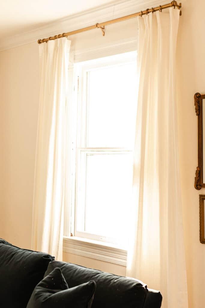 pleated ikea Rivta curtains hung with brass curtain clips on a brass curtain rod